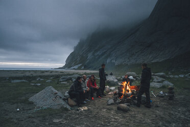 Norway, Lofoten, Moskenesoy, Group of young men sitting at a campfire at Bunes Beach - GUSF00849