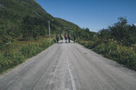 Norway, Lofoten, Moskenesoy, Young men hiking on road to Selfjord - GUSF00876