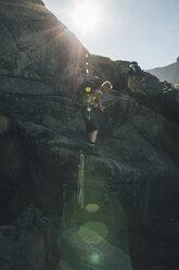 Norway, Lofoten, Moskenesoy, Young men men climbing rocks - GUSF00882