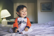 Portrait of laughing baby girl wearing jumpsuit sitting on bed - GEMF01995