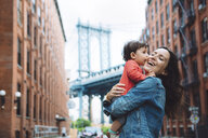 USA, New York, New York City, Baby kissing mother in Brooklyn with Manhattan Bridge in the background - GEMF02004