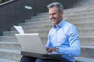Portrait of businessman sitting on stairs using laptop - DIGF04340