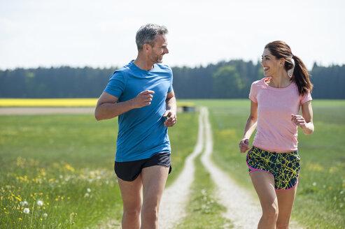 Couple running on field path - DIGF04349