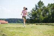 Young woman running on meadow - DIGF04352