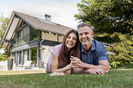 Portrait of happy couple lying in garden of their home - DIGF04370