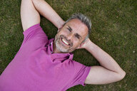 Portrait of smiling mature man lying in grass - DIGF04373