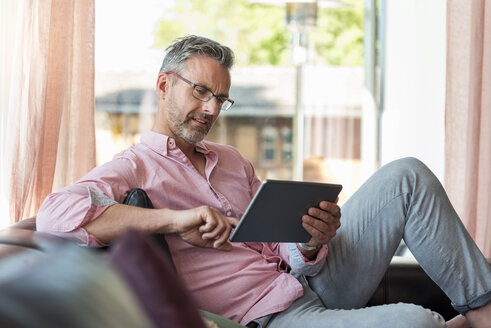 Mature man sitting on couch at home using a tablet - DIGF04385