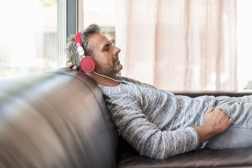 Relaxed mature man lying on couch at home wearing headphones - DIGF04388
