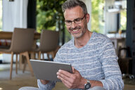 Smiling mature man at home using a tablet - DIGF04394