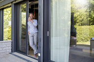 Smiling mature standing at French door at home drinking from glass - DIGF04397