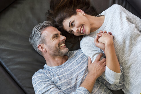 Happy couple lying on couch at home - DIGF04406