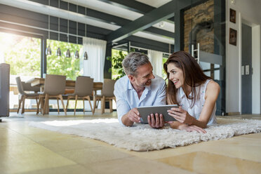Happy couple lying on carpet at home sharing a tablet - DIGF04415
