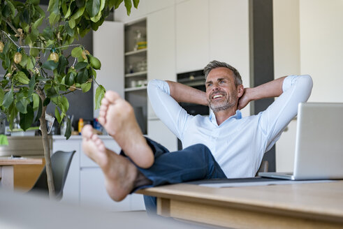 Smiling mature man relaxing at home with laptop on table - DIGF04424