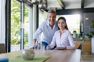 Portrait of smiling couple at table at home - DIGF04427