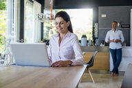 Smiling woman at home using a laptop at table with man in background - DIGF04430