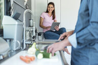 Happy couple in kitchen at home cooking and using a tablet - DIGF04442