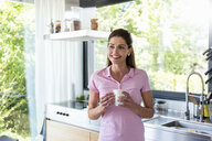 Smiling woman at home in kitchen with cup of coffee - DIGF04448