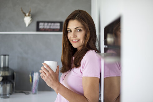 Portrait of smiling woman at home in kitchen with cup of coffee - DIGF04454