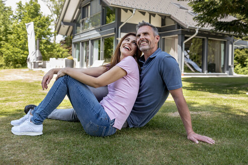 Happy couple sitting in garden of their home - DIGF04466