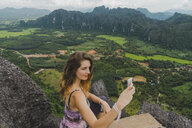 Laos, Vang Vieng, young woman on top of rocks taking a selfie - AFVF00519