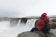 Iceland, North of Iceland, young man photographing waterfall - AFVF00531