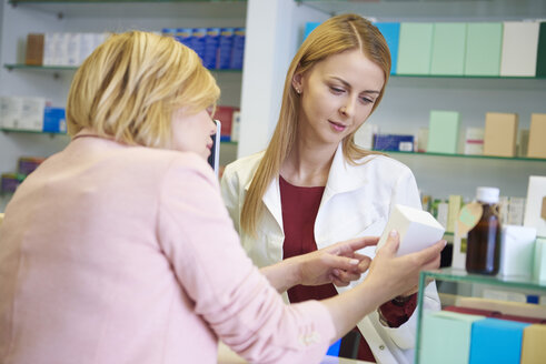 Woman discussing product with pharmacist in pharmacy - ABIF00395