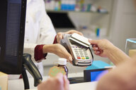 Customer paying cashless with credit card in a pharmacy - ABIF00398