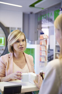 Woman discussing product with pharmacist in pharmacy - ABIF00407
