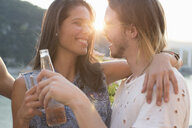 Happy young couple at sunset roof terrace party, Budapest, Hungary - ISF02195