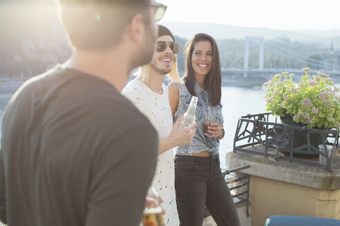 Three adult friends partying on waterfront roof terrace, Budapest, Hungary - ISF02207