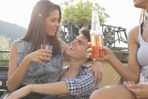 Young couple flirting at roof terrace party - ISF02219