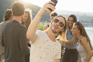 Young man taking selfie at waterfront roof terrace party, Budapest, Hungary - ISF02237