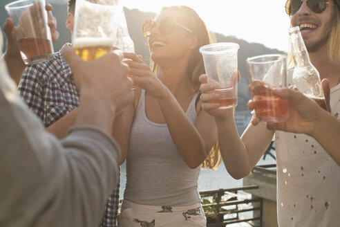 Adult friends raising a toast at roof terrace party, Budapest, Hungary - ISF02246