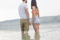 Couple holding hands by river - ISF02267
