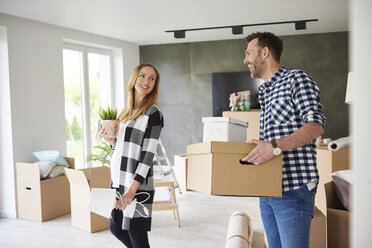 Happy couple moving house carrying cardboard box and plant - ABIF00419