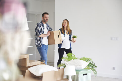 Happy couple moving into new flat carrying cardboard box and plant - ABIF00422