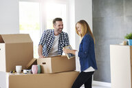 Couple moving into new flat packing cardboard boxes - ABIF00425