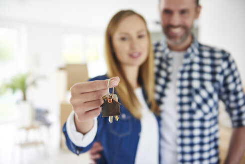 Close-up of couple holding key to new home - ABIF00431