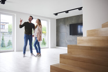 Couple looking around in empty flat - ABIF00434