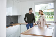 Couple examining kitchen in new flat - ABIF00440