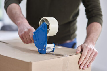 Close-up of man taping cardboard box - ABIF00446