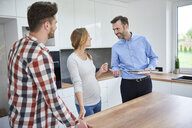 Couple and real estate agent talking in kitchen of new apartment - ABIF00449