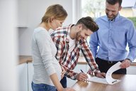 Couple with real estate agent signing contract in kitchen of new apartment - ABIF00452