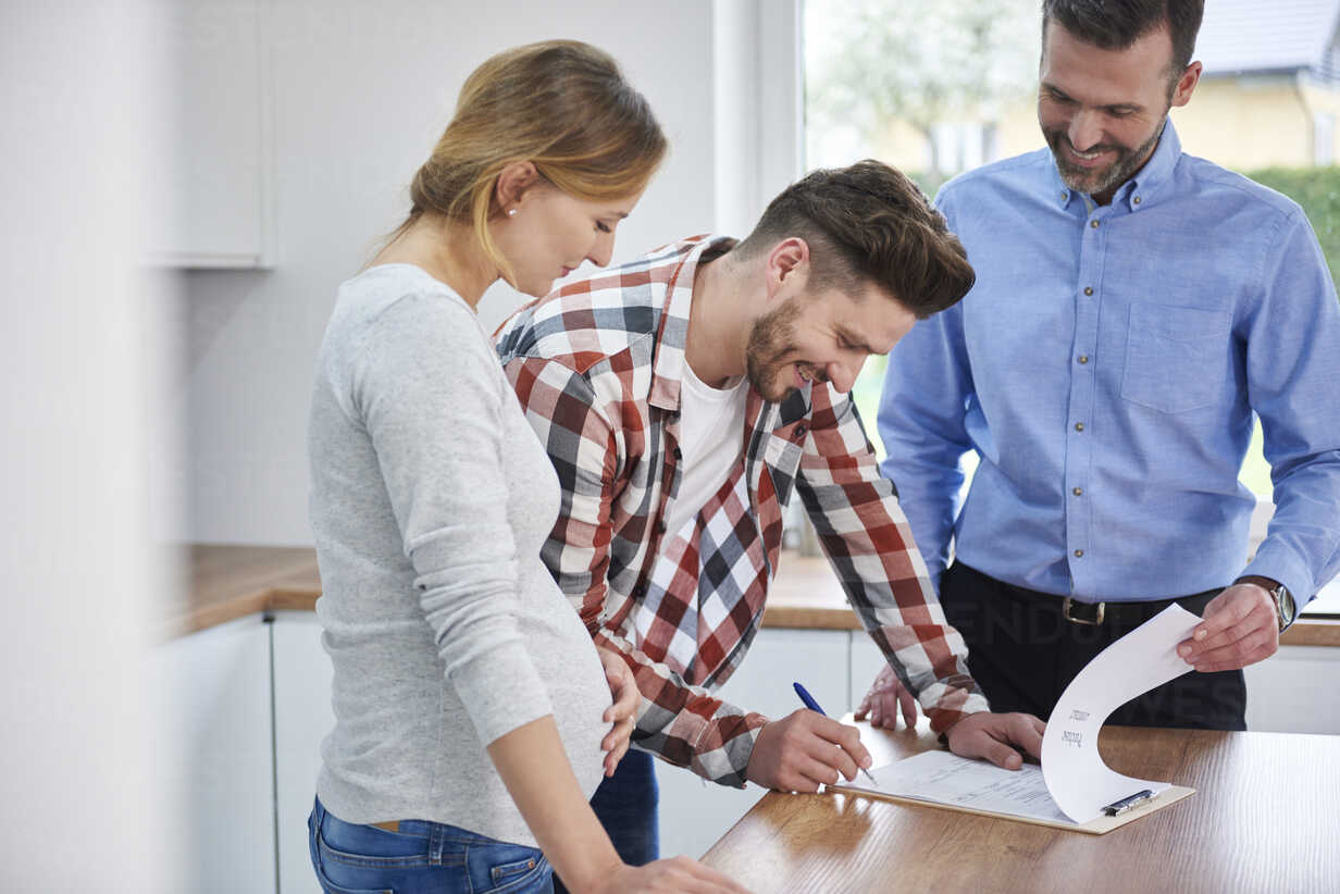 Couple with real estate agent signing contract in kitchen of new apartment - ABIF00452 - gpointstudio/Westend61