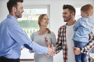 Family and real estate agent shaking hands in new apartment - ABIF00458