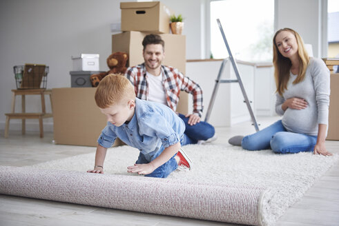 Boy with parents unrolling a carpet in new flat - ABIF00464