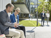 Colleagues with tablet sitting on bench outside office building - CVF00589