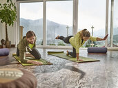Couple practicing yoga in a room with panorama window - CVF00595