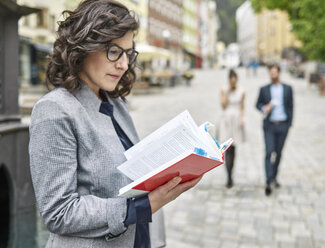 Businesswoman reading book in the city - CVF00604