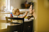 Father helping young son at meal time - ISF02365